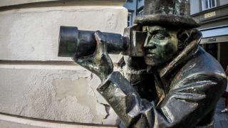 Bronzestatue lugt mit Teleobjektiv um eine Ecke